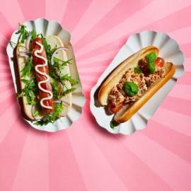 Hotdogs in ontbijtspek met rucola en rode ui
